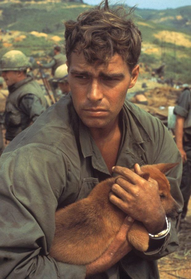 American soldier cradling a dog while under siege at Khe Sanh, Vietnam, 1968. Photograph by Larry Burrows.